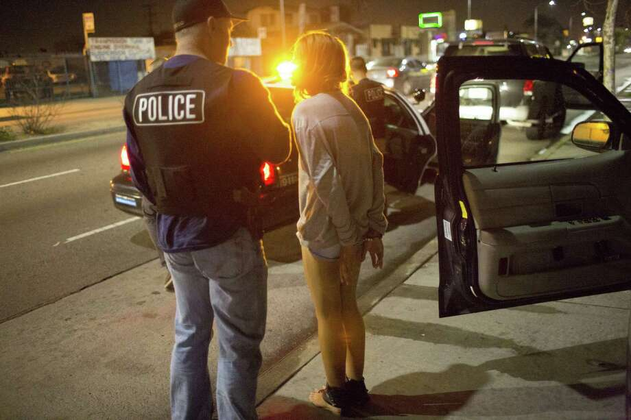 LOS ANGELES, CA - FEBRUARY 2: A 17-year old girl in hand-cuffs is questioned February 2, 2013 by a vice squad policeman, Sergeant Brian Gallagher, with the Los Angeles Police Department's South Central's 77th Street Division about committing prostitution in Los Angeles, California. While the charge of soliciting or loitering with the intent to commit prostitution is a misdemeanor, the girl will be held for 2-4 days. As a minor, the girl was formally charged with loitering with the intent to engage in acts of prostitution. The majority of juveniles arrested for prostitution in Los Angeles county come from the city's foster care program. In 2010, police in Los Angeles arrested 174 juveniles for prostitution. In South Central Los Angeles, prostitution flourishes and is often controlled by pimps who are former Bloods or Crips gang members. Photo: Robert Nickelsberg, Getty Images / 2013 Robert Nickelsberg