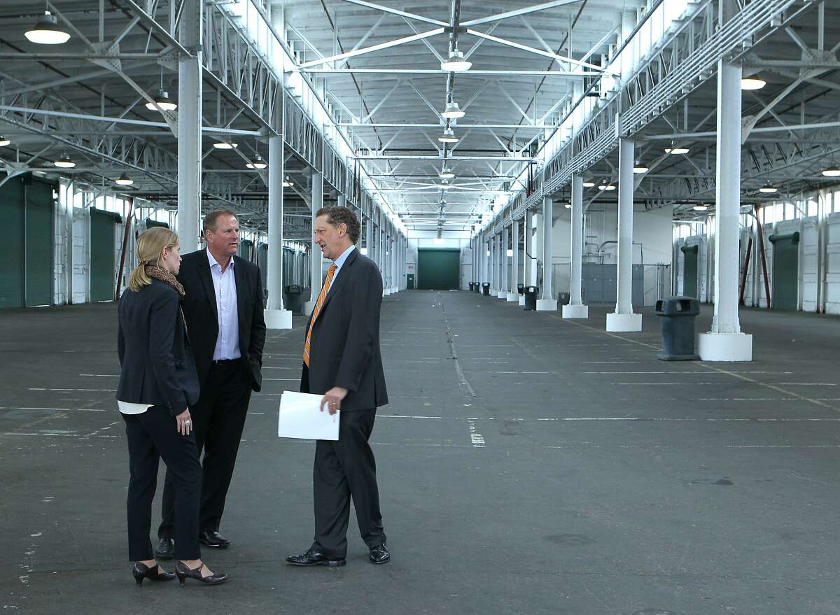 Giants CEO Larry Baer (right), vice president Jack Bair (center) and director of development Fran Weld talk about the proposed development for Lot A, Monday, May 4, 2015, in San Francisco, Calif. Pier 48 (pictured) would be Anchor Brewing's new location.