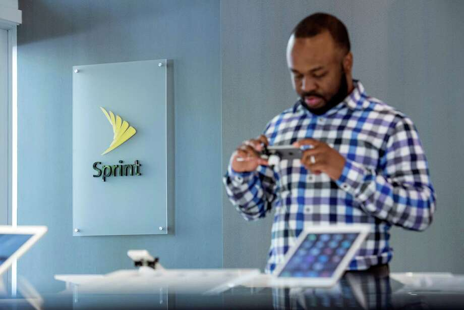 A customer looks at an Apple Inc. iPhone 6 at a Sprint Corp. store in Palo Alto, Calif. (David Paul Morris/Bloomberg) Photo: David Paul Morris / © 2015 Bloomberg Finance LP