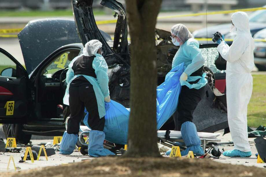 A crew removes the bodies of two gunman outside the Curtis Culwell Center where the shooters opened fire Sunday night at an event where people were invited to present cartoons of the Prophet Muhammad, before they were shot and killed by police officers in Garland. One of the two gunmen was identified on Monday by a law enforcement official as a man who had previously been labeled by the FBI as a jihadist terrorism suspect. (Cooper Neill/The New York Times) Photo: COOPER NEILL, STR / NYTNS