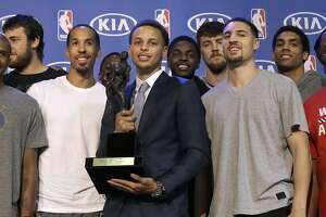 Golden State Warriors guard Stephen Curry, center, poses for photos with teammates and coaches at a basketball news conference announcing him as the NBA's Most Valuable Player Monday, May 4, 2015, in Oakland, Calif. Curry carried the top-seeded Warriors to a franchise-record 67 wins and surpassed his own record for most 3-pointers in a season. (AP Photo/Jeff Chiu)
