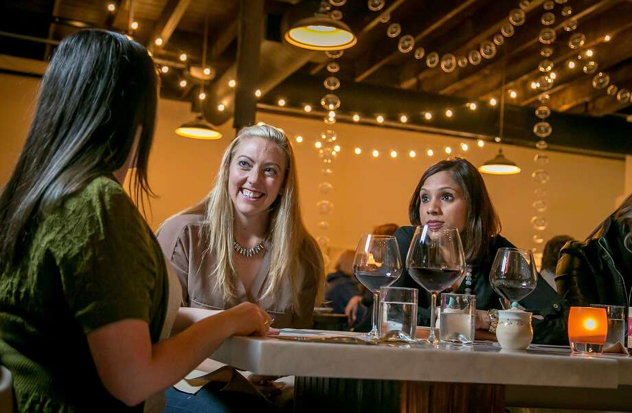 At A16 in Oakland, Lauren Cardinet (left), Leslie Henthorn and Kelly Hansen have wine at the bar.  Photo: John Storey, Special To The Chronicle