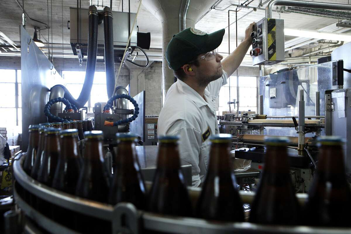 Peter checks the beer bottles for any imperfections at Anchor Brewing, Monday, April 27, 2015, in San Francisco, Calif.