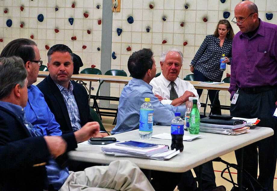 Members of the Representative Town Meeting talk prior to Monday's annual budget meeting. Photo: Genevieve Reilly / Fairfield Citizen