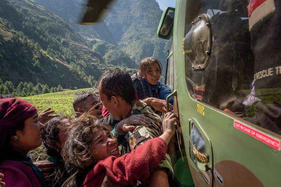 A military official aims to keep back villagers trying to force their way onto a helicopter in Bihi, Nepal, during a relief mission. Photo: Daniel Berehulak /New York Times / NYTNS