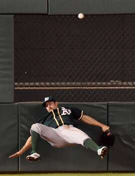 MINNEAPOLIS, MN - MAY 4: Billy Burns #1 of the Oakland Athletics hits the center field wall after missing a catch of the double hit by Eduardo Escobar #5 of the Minnesota Twins during the eighth inning of the game on May 4, 2015 at Target Field in Minneapolis, Minnesota. The Twins defeated the Athletics 8-7. (Photo by Hannah Foslien/Getty Images)