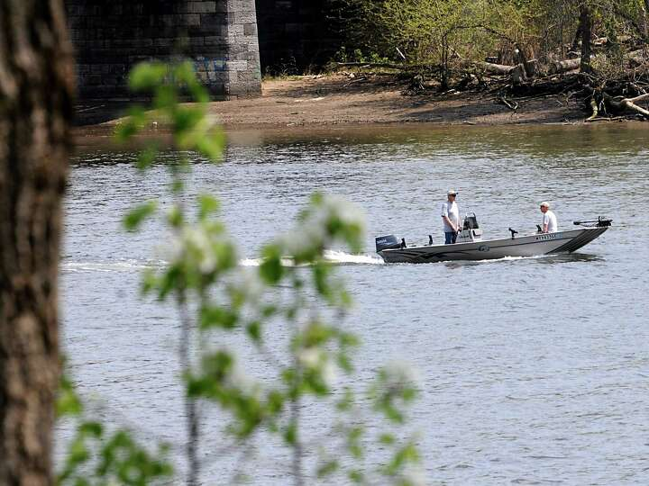 A couple of fishermen ride down the Hudson River in a fishing boat near the Corning Preserve on Mond