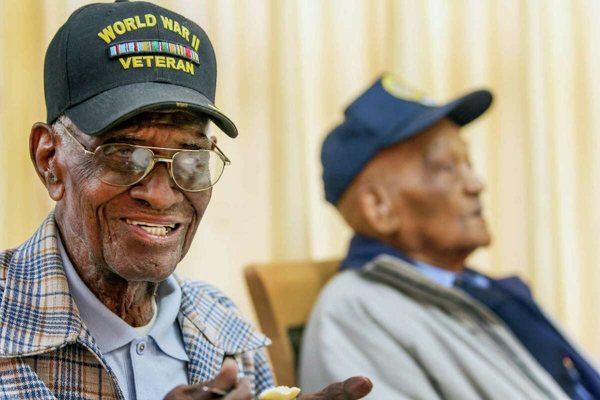 Richard Overton, 107, left, smiles as he finishes his meal at the Emeritus at Parmer Woods on Friday, Dec. 13, 2013, in Austin, Texas. Austin Texas Mayor Lee Leffingwell presented a proclamation acknowledging and thanking Overton, and Elmer Hill, 107, right, for their service. Overton is Austin's oldest living World War II veteran and Hill is Henderson, Texas' oldest living World War II veteran. (AP Photo/Austin American-Statesman, Ricardo Brazziell) AUSTIN CHRONICLE OUT, COMMUNITY IMPACT OUT, MAGS OUT; NO SALES; INTERNET AND TV MUST CREDIT PHOTOGRAPHER AND STATESMAN.COM