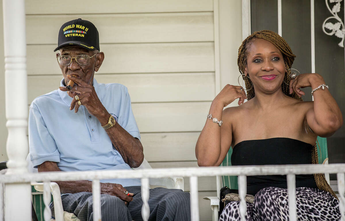 Richard Overton, left, smokes a cigar with friend Donna Shorts. Overton is considered to be the oldest living World War II veteran in the United States celebrated his 109th birthday on a front porch in East Austin, Texas, on Sunday, May 3, 2015, with friends and family. (Ricardo B. Brazziell/Austin American-Statesman via AP)