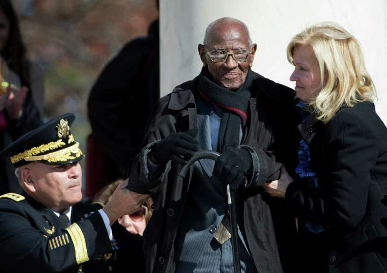 Richard Overton, the oldest living WWII veteran, center, is assisted during a Veterans Day ceremony,