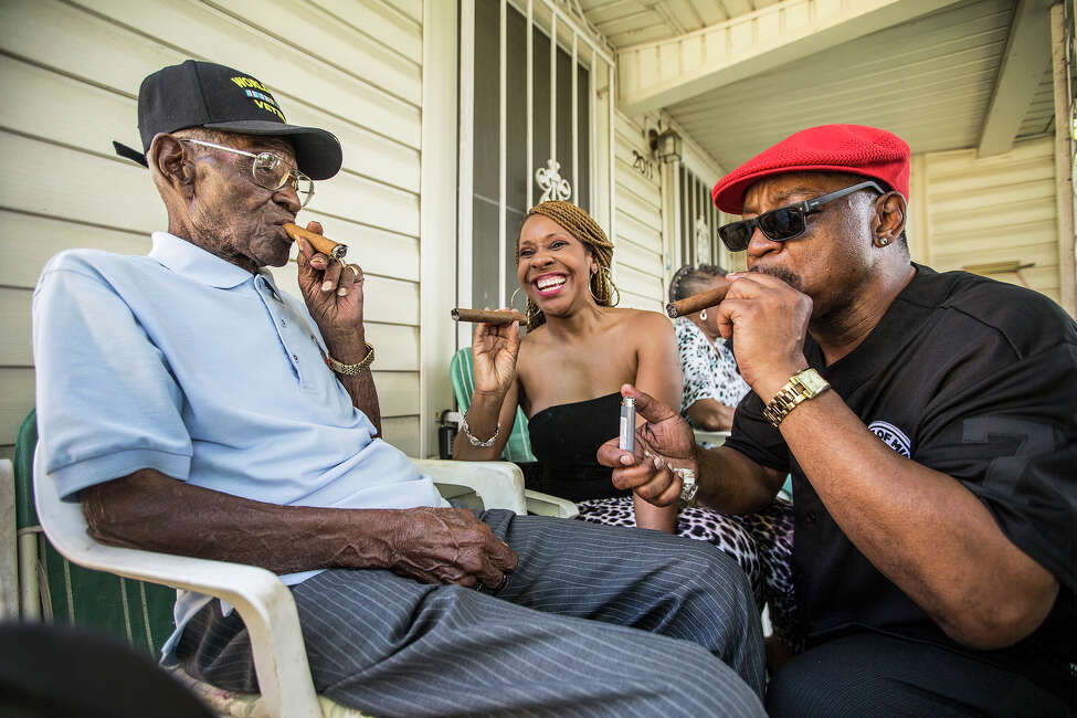 Richard Overton, left, smokes a cigar with a few neighborhood friends Donna Shorts, center and Martin Wilford Sunday, May 3, 2015, in Austin, Texas.. Overton, is considered to be the oldest living World War II veteran in the United States, celebrated his 109th birthday on a front porch in East Austin with friends and family. Wilford, right, says that he has known Overton for 37 years and he looks at Mr. Overton as if he was his biological father. (Ricardo B. Brazziell/Austin American-Statesman via AP)