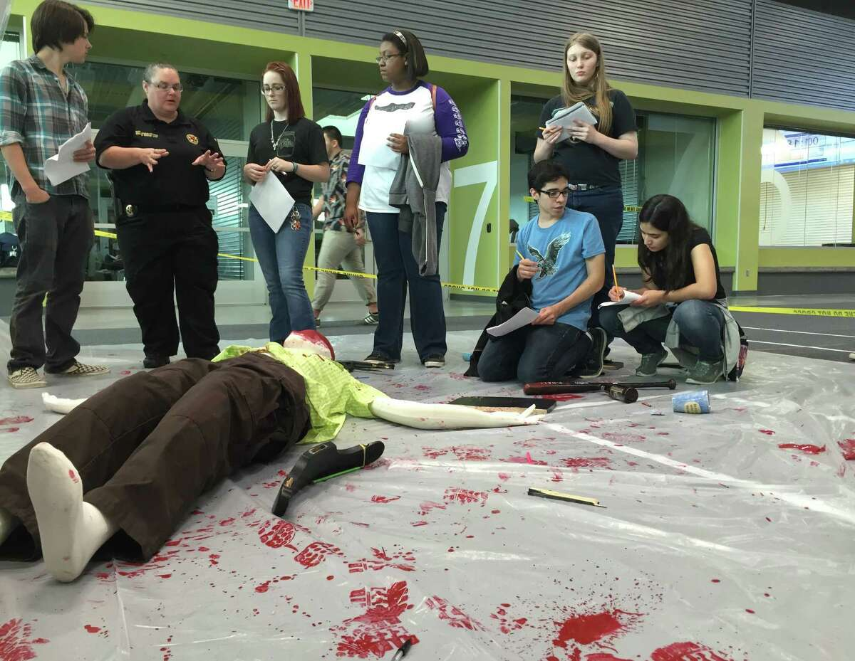 Students in Katy Independent School District's new forensic science course work with a Fort Bend County Sheriff's Office investigator April 24 to solve a mock murder set up for them as part of a field trip to the Robert R. Shaw Center for Science, Technology, Engineering, Arts and Mathematics that opened in February.