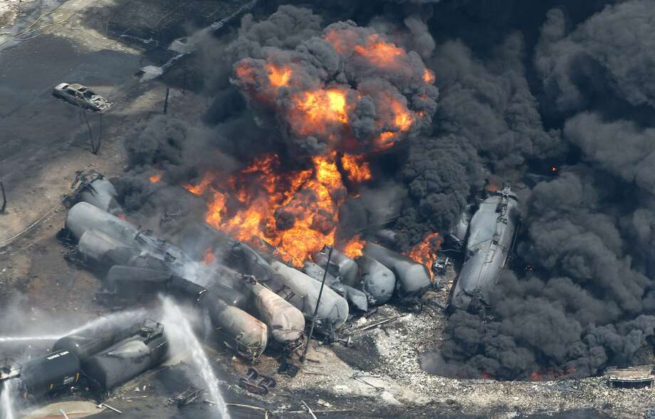 Smoke rises from railway cars that were carrying crude oil after derailing in downtown Lac Megantic, Quebec. Photo: Paul Chiasson, Associated Press