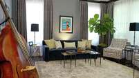"The formal living room has become the ""jazz room,"" with cool shades of blue and gray and John Esquivel's double bass propped in a corner."