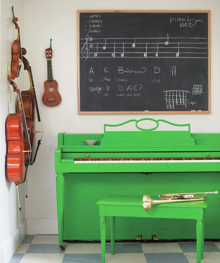 Mom design blogger Gabrielle Blair gives an old piano new life with a fresh coat of green paint. Instruments on the wall double as art. Photo: Kristen Loken / Kristen Loken / ONLINE_YES