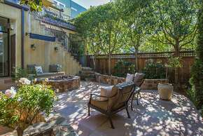 Mature trees help shade the backyard and its tile patio.