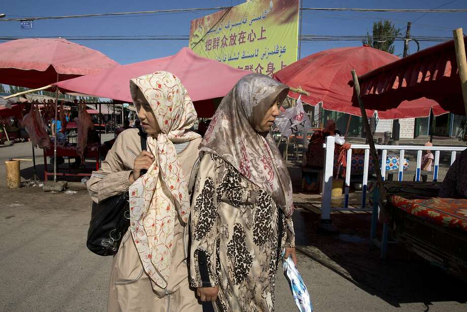 """Uighur women in loose, full-length garments and headscarves associated with conservative Islam visit a market in Alaqagha in western China's Xinjiang province.  In China's restive western province of Xinjiang, young men of the Uighur ethnic minority are not allowed to have beards. Also proscribed are certain types of women's headscarves, veils and """"jilbabs,"""" loose, full-length garments worn in public. Such restrictions are not new but their enforcement has intensified this year in the wake of attacks Beijing has blamed on religious extremists. Photo: Ng Han Guan, AP"""