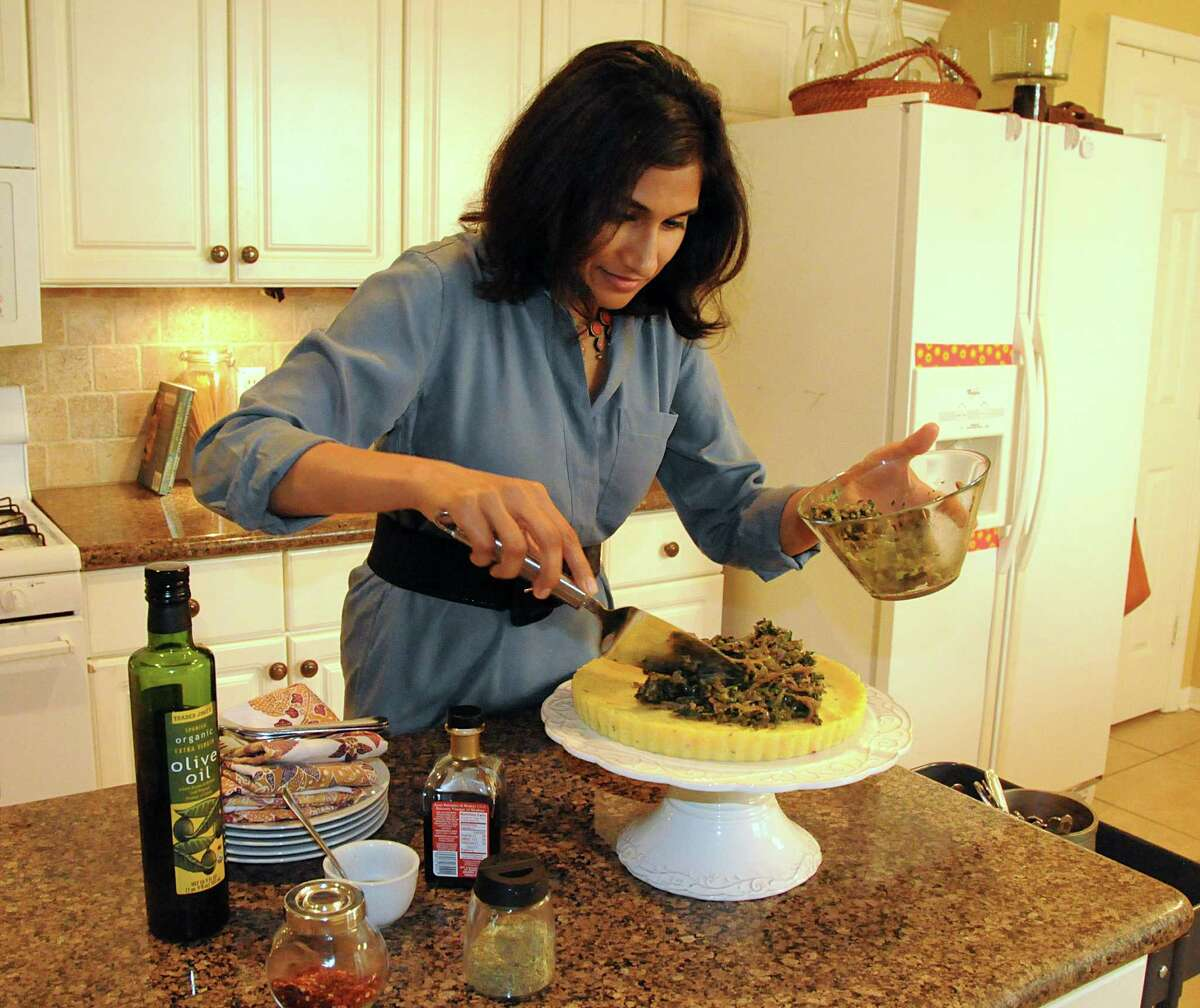Vegan chef Kala Ganapathy prepares a polenta tart using wilted greens at her home in The Woodlands. Ganapathy is also a vegan personal chef and cooking instructor. Photograph by David Hopper.