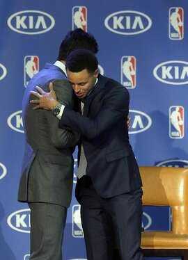 Golden State Warriors guard Stephen Curry, right, hugs general manager Bob Myers at a basketball news conference announcing Curry as the NBA's Most Valuable Player Monday, May 4, 2015, in Oakland, Calif. Curry carried the top-seeded Warriors to a franchise-record 67 wins and surpassed his own record for most 3-pointers in a season. (AP Photo/Jeff Chiu)