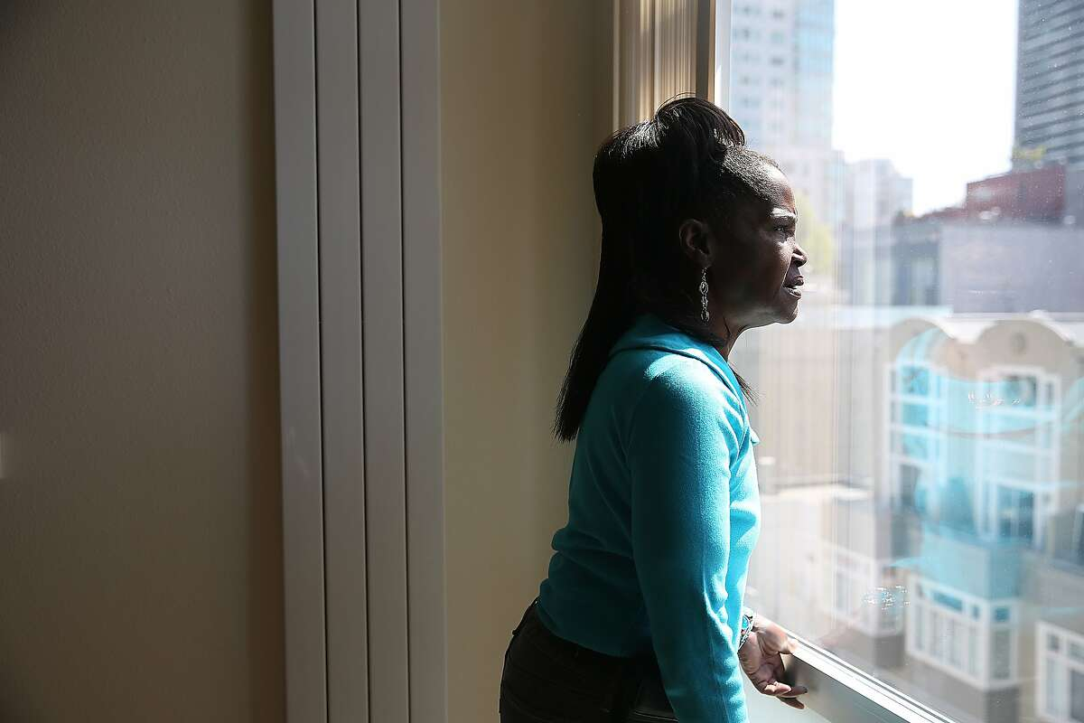 Wanda Demus, 61, looks out of her apartment window before she gets ready to head to a medical appointment at UCSF in San Francisco, California, on Tuesday, May 5, 2015.