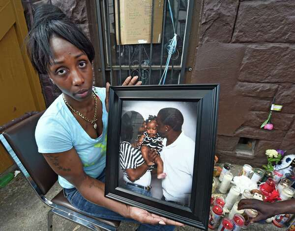 Robin Williams, fiancŽ  of Courtney Yates, who was murdered early this morning in a multiple shooting, holds a photo of herself and their child Elegent Yates, at a memorial near the shooting scene at 117 Lark Street Tuesday May 5, 2015 in Albany, N.Y.    (Skip Dickstein/Times Union) Photo: SKIP DICKSTEIN