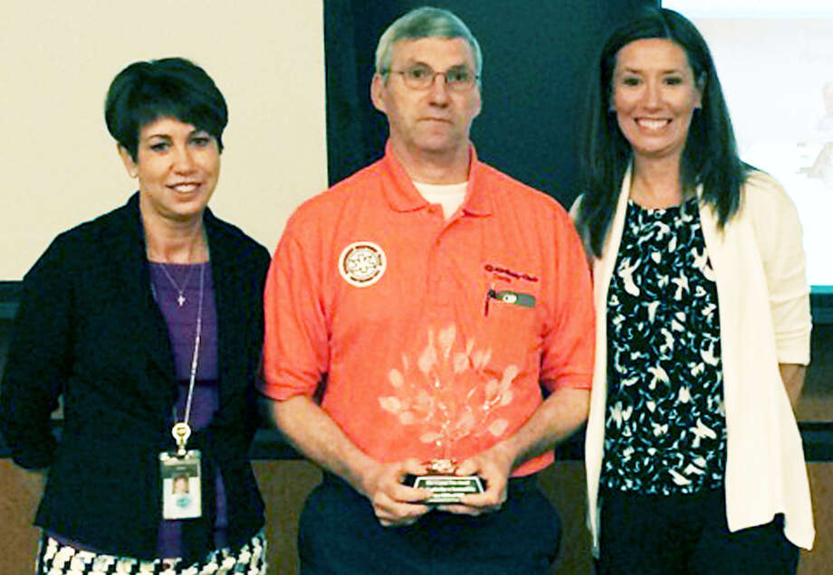 Denis Larkin, the New Milford millâÄôs environmental health and safety manager, is on hand to receive the local plant's Crystal Tree award from Gail Ciccione, left, Kimberly-Clark's vice president for global safety, quality and sustainability, and Lisa Morden, senior director of sustainability. May 2015  Courtesy of Kimberly-Clark Photo: Contributed Photo / The News-Times Contributed