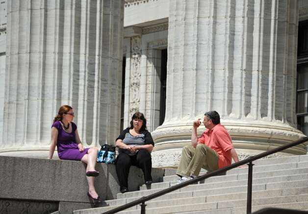New York State Education Department employees Karen Salisbury of Troy, left, Debbie Carle of Clifton Park and Rob Smith of Clifton Park enjoy a sunny day by sitting on the steps outside their building on Tuesday, May 5, 2015 in Albany, N.Y.  (Lori Van Buren / Times Union) Photo: Albany Times Union