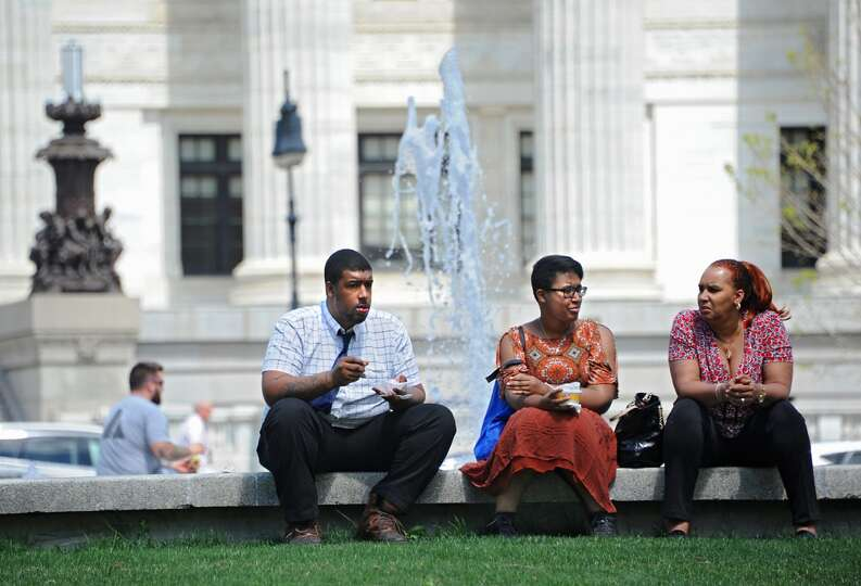 From left, Nigel and Niara Banks of Albany sit with their mother Celeste Night of Albany near a foun