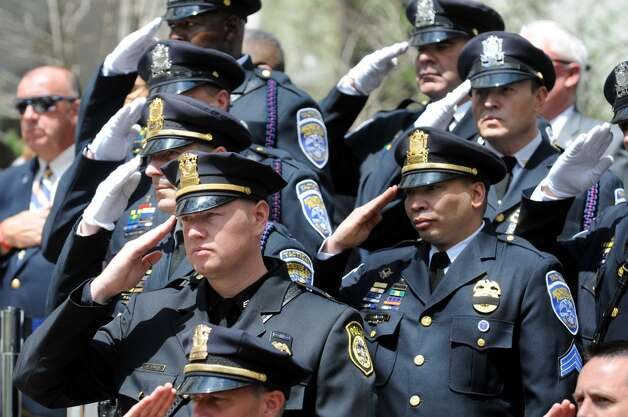 Police officers stand at attention as the National Anthem is played during a police officers memorial ceremony on Tuesday, May 5, 2015, at the State Police Memorial in Albany, N.Y. Nine officers, who died from line of duty injuries in 2014, were honored. (Cindy Schultz / Times Union) Photo: Albany Times Union