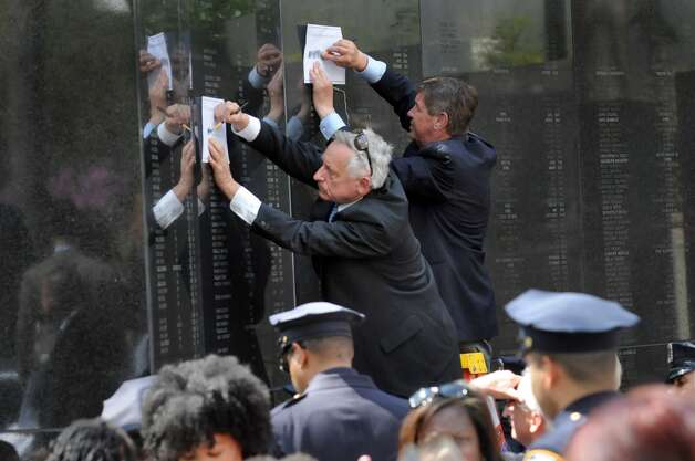 Tom Canning, left, and Michael Locken, both of New York State Criminal Justice Services. etch names for family members following a police officers memorial ceremony on Tuesday, May 5, 2015, at the State Police Memorial in Albany, N.Y. Nine officers, who died from line of duty injuries in 2014, were honored. (Cindy Schultz / Times Union) Photo: Albany Times Union