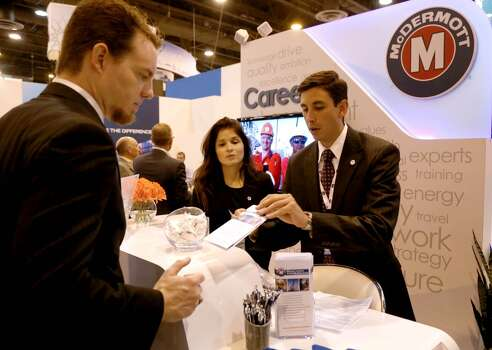 Michael Friday, left, of Kemah, shown with Sabrina Sierra, and Juan Castelblanco, both of McDermott, looks for employment at the McDermott Production Systems career booth in the  Offshore Technology Conference at the NRG Center Tuesday, May 5, 2015, in Houston, Texas. ( Gary Coronado / Houston Chronicle ) Photo: Gary Coronado, Houston Chronicle