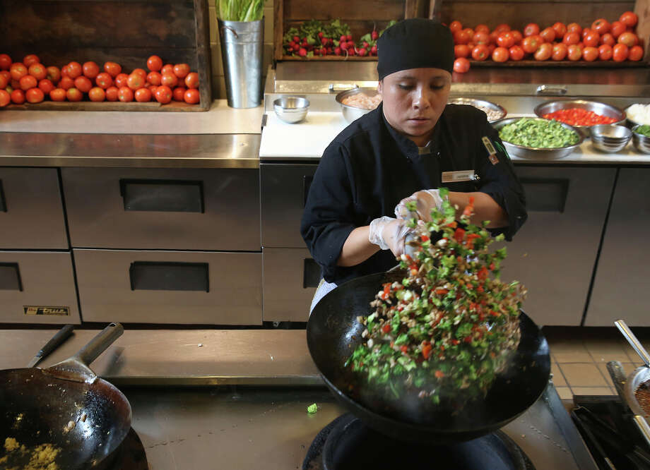 Line cook Carolina Chavez makes broccoli togarashi at the cafeteria at Dominican University in San Rafael, which is run by Bon Appetit Management Co. Bon Appetit's program Imperfectly Delicious uses produce that might otherwise be thrown out because of aesthetic reasons. Photo: Liz Hafalia / The Chronicle / ONLINE_YES