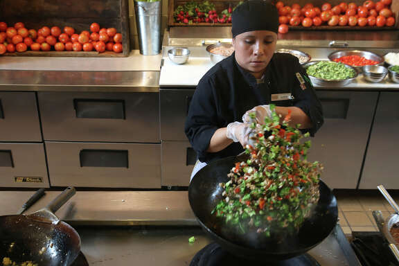 Line cook Carolina Chavez makes broccoli togarashi at the cafeteria at Dominican University in San Rafael, which is run by Bon Appetit Management Co. Bon Appetit's program Imperfectly Delicious uses produce that might otherwise be thrown out because of aesthetic reasons.