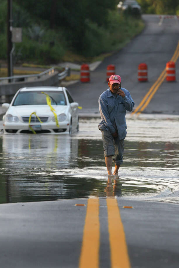 """Luis Javier Frausto,58, talks on his cell phone Friday May 11, 2012 while standing in the waters of Rosillo creek that flowed over a recently constructed bridge on south W.W. White road near Hildebrandt road. Earlier around 5:45 a.m., a woman drove her Mercedes into the flood swollen creek after rain fell in the area Thursday night. The woman was helped out of her car by San Antonio firefighters and was not harmed. """"What's the purpose of making a new bridge if it's not going to stop the flooding ?"""" Frausto said. Frausto, who lives nearby, said this is the second time he's seen flood waters over the new bridge since it was completed. John Davenport/San Antonio Express-News Photo: JOHN DAVENPORT, STAFF / SAN ANTONIO EXPRESS-NEWS / SAN ANTONIO EXPRESS-NEWS (Photo can be sold to the public)"""