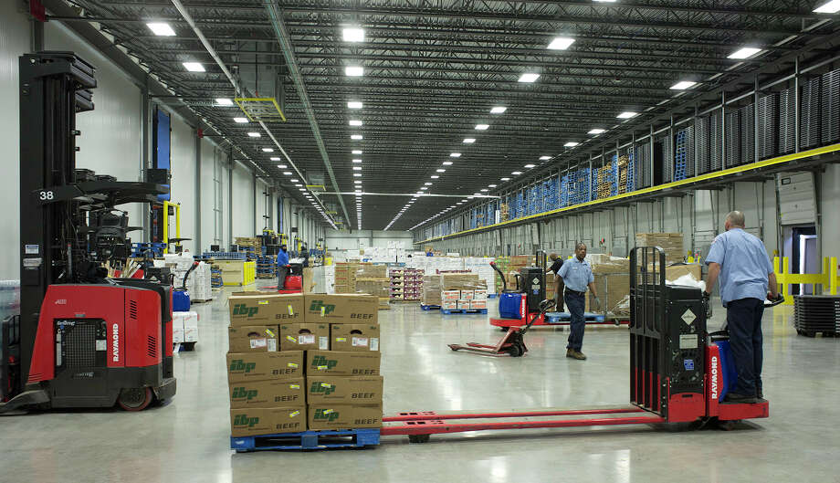 Produce and other food-service items are unloaded from trucks through sealed cargo bays at the Sysco distribution center in Schertz. Tuesday's ruling means the Sysco and US Foods cannot move forward with the merger without further review. Photo: Express-News File Photo / The San Antonio Express-News