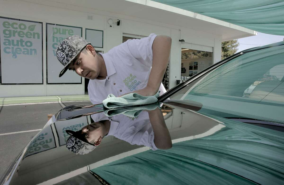 Crew member Jose Salazar polishes a vehicle to a mirror finish at the Eco Green Auto Clean Car Wash in Redwood City , Calif., as seen on Tues. May 5, 2015.