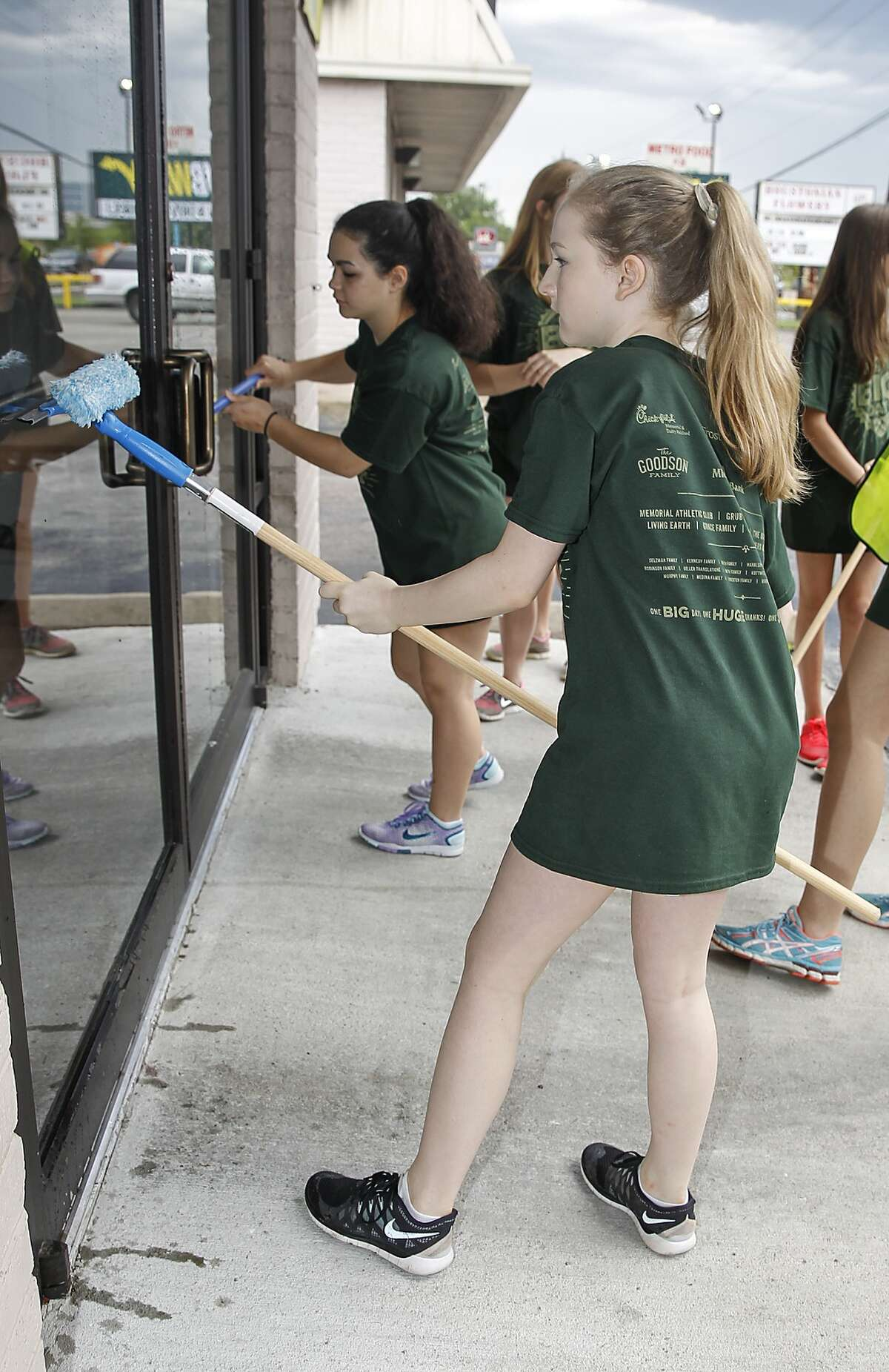 Cheerleader Robin Graves cleans windows at a local business as part of Stratford's Big Day, a student run volunteer initiative where hundreds of Stratford students will be working on improvement projects for local businesses, needy individuals and at the school on April 25, 2015.