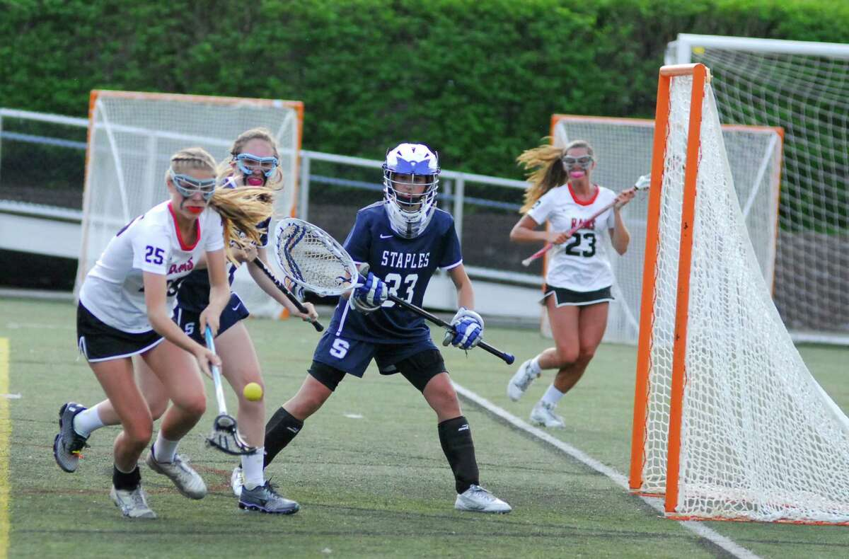 New Canaan's Campbell Armstrong, left, picks up a loose ball in front of the cage while Staples goalie Alexa Moro looks on during a game on Tuesday. New Canaan won 14-4