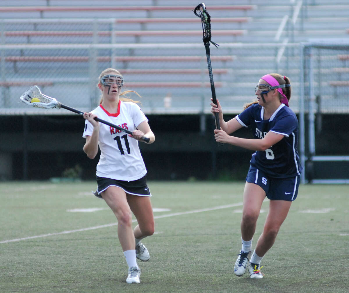 New Canaan's Madeline Gertsen, left, looks to make a pass while Staples defender Amelia Heisler looks on during a game on Tuesday. New Canaan won 14-14.