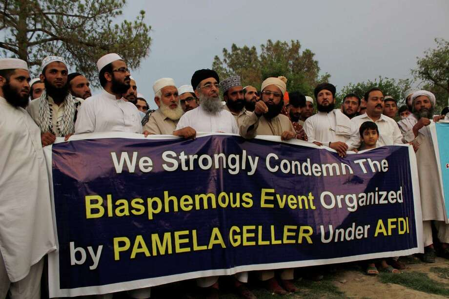 People hold a banner at a park in Peshawar, Pakistan, to condemn an organizer for the cartoon event in Garland on Sunday that left the two gunmen dead. Photo: Mohammad Sajjad /Associated Press / AP