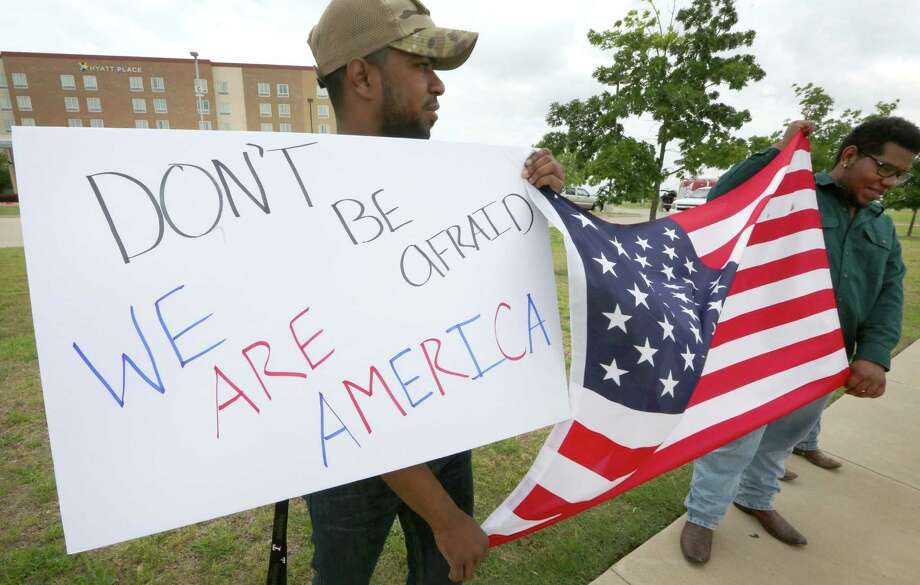 Joseph Offutt (left) and Raheem Peters hold a sign and a U.S. flag across the street from the Curtis Culwell Center in Garland. Photo: LM Otero /Associated Press / AP