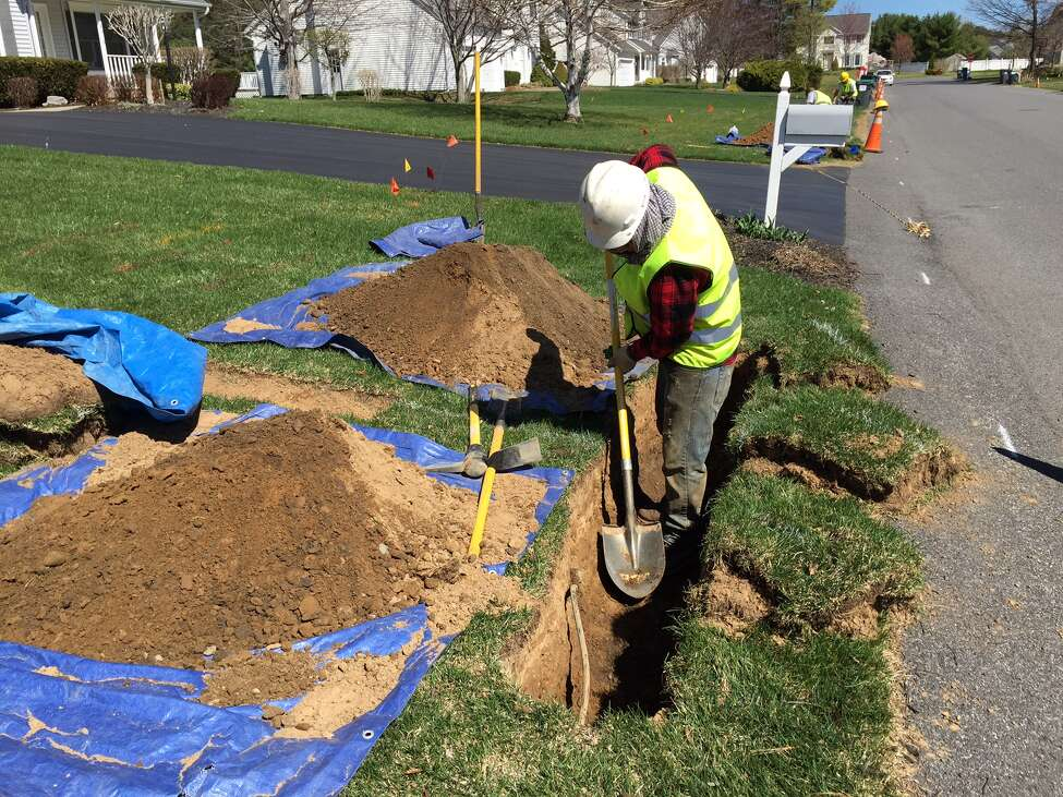 Workers from a half-dozen countries dig a trench while installing a fiber-optic network pipe for Verizon FiOS in the Random Acres development of Guilderland. They work 12-hour days for $150 a day. (Paul Grondahl / Times Union)