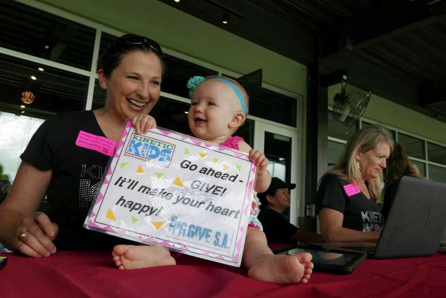 ABOVE: Kinetic Kids staffer Natalie Henry enjoys her daughter, Vivian, at the group's display at Top Golf as part of The Big Give on Tuesday, May 5, 2015; a day during which charities and other groups receive donations via crowdfunding. Kinetic Kids provides health, education and recreation services for children living with cerebral palsy, spina bifida, Down's syndrome, Asperger's syndrome and many other conditions. Photo: Billy Calzada / San Antonio Express-News / San Antonio Express-News