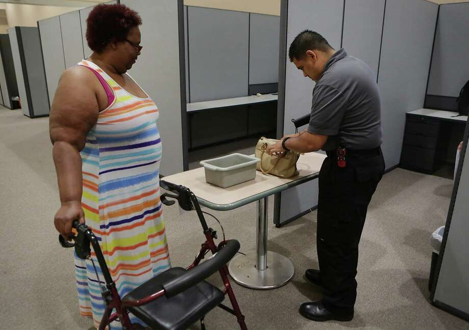 Vivian Childress, left, a probationer, waits at the security check point as Richard Luebano, a security officer, goes through her personal items.  Childress was meeting with Nicole Lary her Community Supervision Officer at the SAHA Grant funded one-stop initiative called the Resurgence Collaborative, housed at the Barbara Jordan Center, on Monday, May 4, 2015. Photo: Bob Owen, Staff / San Antonio Express-News / San Antonio Express-News