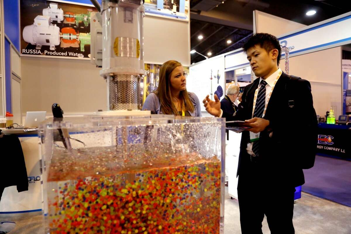 Colored plastic balls are used to show the flow of circulation of a disc pack from a disc mixer at the Discflo Disc Pumps, of California, booth at the Offshore Technology Conference at the NRG Center Tuesday, May 5, 2015, in Houston, Texas. Erica Couch, of Discflo, and Takashi Okada, of Kawasaki Heavy Industries, Japan, are shown in the photo. ( Gary Coronado / Houston Chronicle )