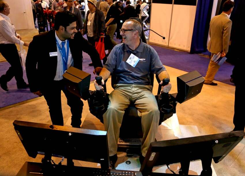 Manas Goyal, left, of MHWirth, Houston, shows Jim Shifrin, of Dixon Valve & Coupling Company, Houston, how to simulate making up pipe on a third generation operator chair at the Offshore Technology Conference at the NRG Center Monday, May 4, 2015, in Houston, Texas. ( Gary Coronado / Houston Chronicle )