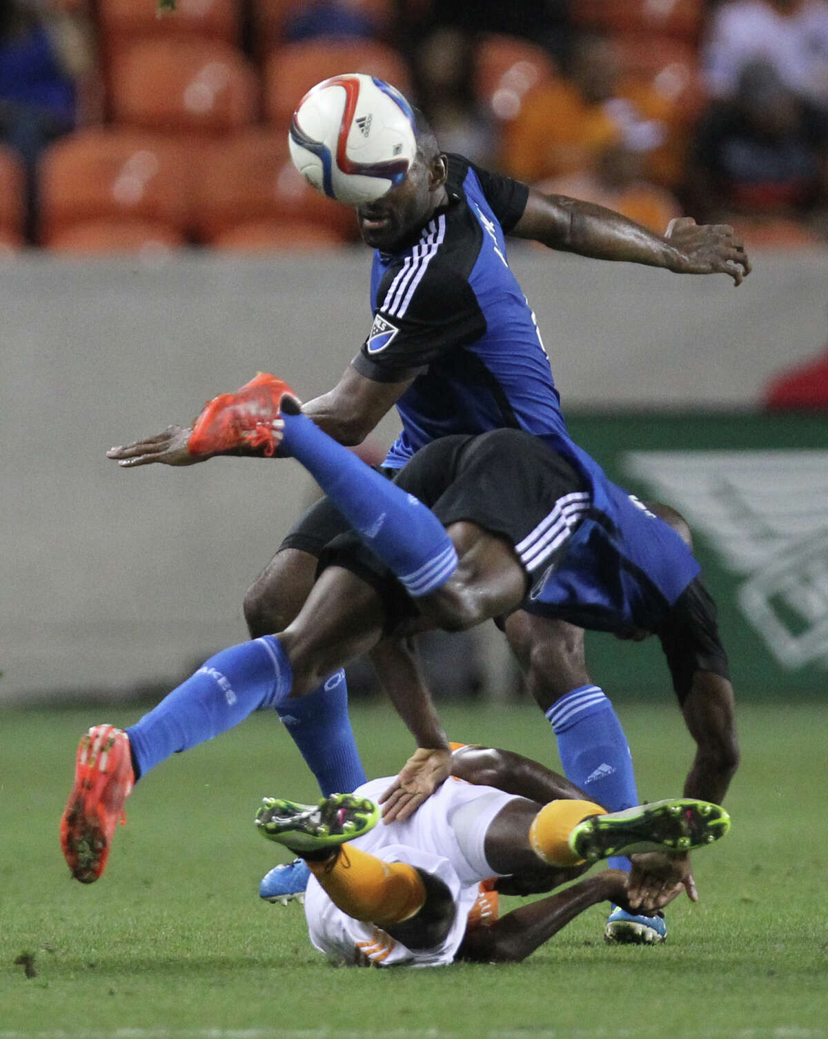 Houston Dynamo defender/midfielder DaMarcus Beasley (7) and San Jose Earthquakes midfielder Sanna Nyassi (17) collapse at the feet of San Jose Earthquakes defender Marvell Wynne (4), Tuesday, May 5, 2015, near the end of the first half, in Houston.