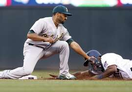 Oakland Athletics shortstop Marcus Semien, left, tags out Minnesota Twins' Torii Hunter after a steal attempt of second base in the first inning of a baseball game, Tuesday, May 5, 2015, in Minneapolis. (AP Photo/Jim Mone)