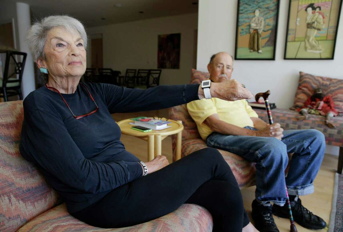 In this March 17, 2015 photo, Dorothy Dworsky, 80, sitting next to her husband, Bill, 81, shows a watch she wears that keeps track of her movements at their home in San Francisco. Each time Bill or Dorothy opens the refrigerator, closes the bathroom door or lifts the lid on a pill container, tiny sensors in their home make notes on a digital logbook, which their son Phil Dworsky monitors daily on his smartphone. (AP Photo/Eric Risberg) ORG XMIT: NYBZ302