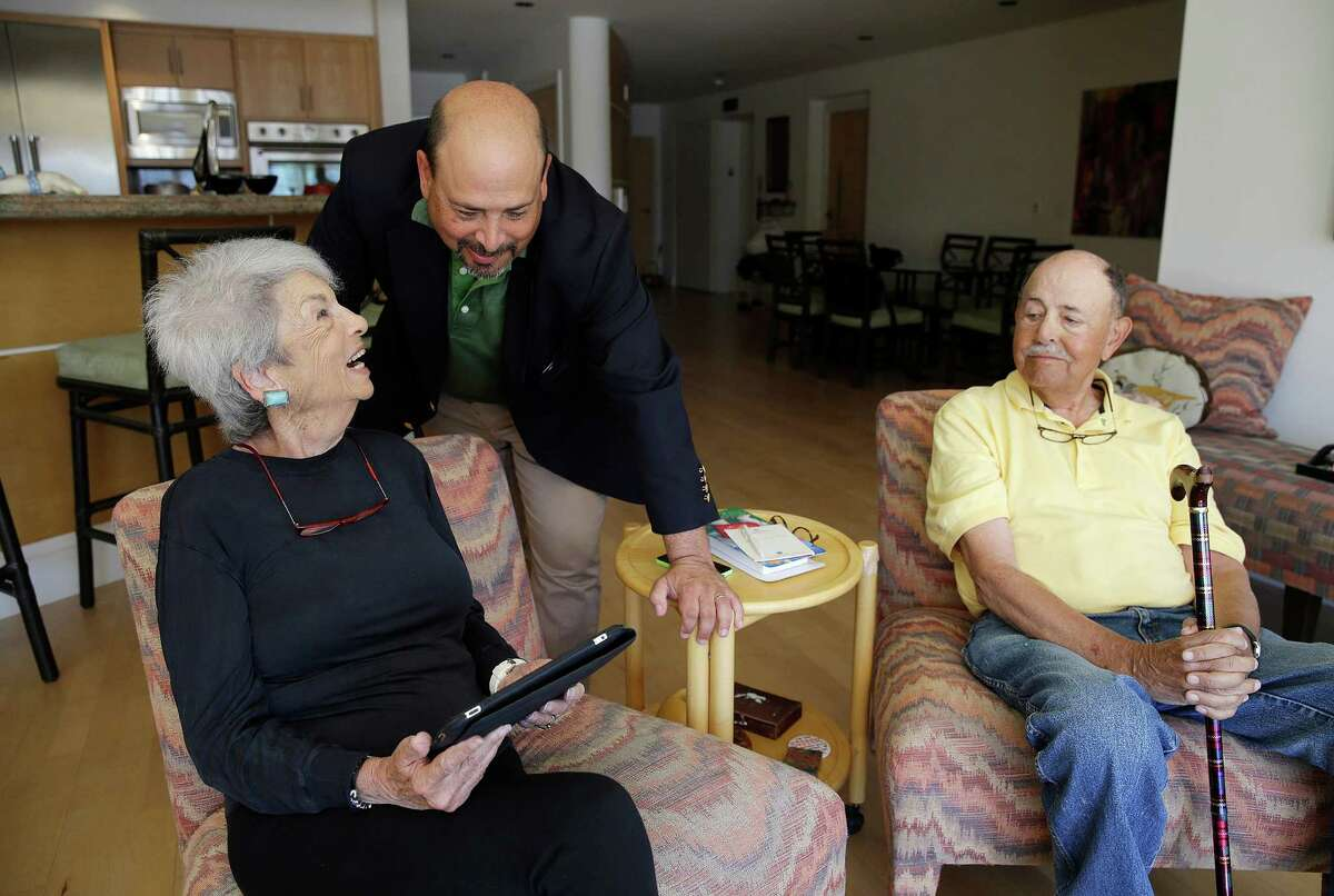 In this March 17, 2015 photo, Phil Dworsky visits with his parents, Dorothy and Bill Dworsky, at their home in San Francisco. Each time an elder Dworksy opens the refrigerator, closes the bathroom door or lifts the lid on a pill container, tiny sensors in their home make notes on a digital logbook, which the younger Dworsky monitors daily on his smartphone. (AP Photo/Eric Risberg) ORG XMIT: NYBZ303
